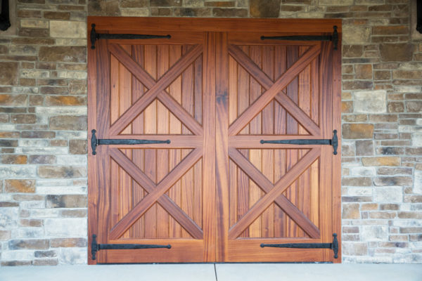 six forged iron door hinges placed on symmetrical wooden door leading into stone building