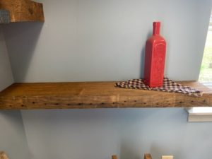 reclaimed wood shelf hung on light blue wall with red bottle and plaid napkin sitting on top